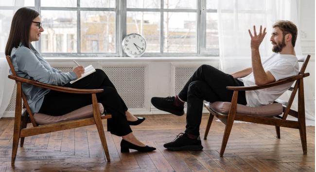 Bilde av to mennesker som sitter på hver sin stol på et kontor. De vender mot hverandre. Kvinnen til venstre skriver i en bok mens mannen til høyre snakker til henne.