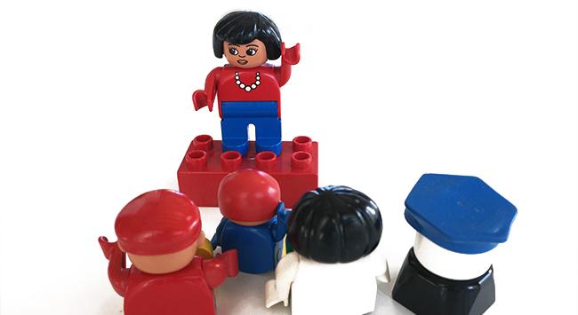 Legodame som taler til en forsamling