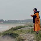 En person står ved en strand i gul kjole og allværsjakke med en hvit stokk. Skogen og husene i bakgrunnen ligger i et tynt lag tåke, og bølger slår inn mot sandstranda.