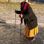 Person går opp en isdekket bakke med to gåstaver med pigger som støtte.